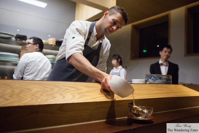 Chef Levy pouring the Buddha hand broth on top of the Belon oyster