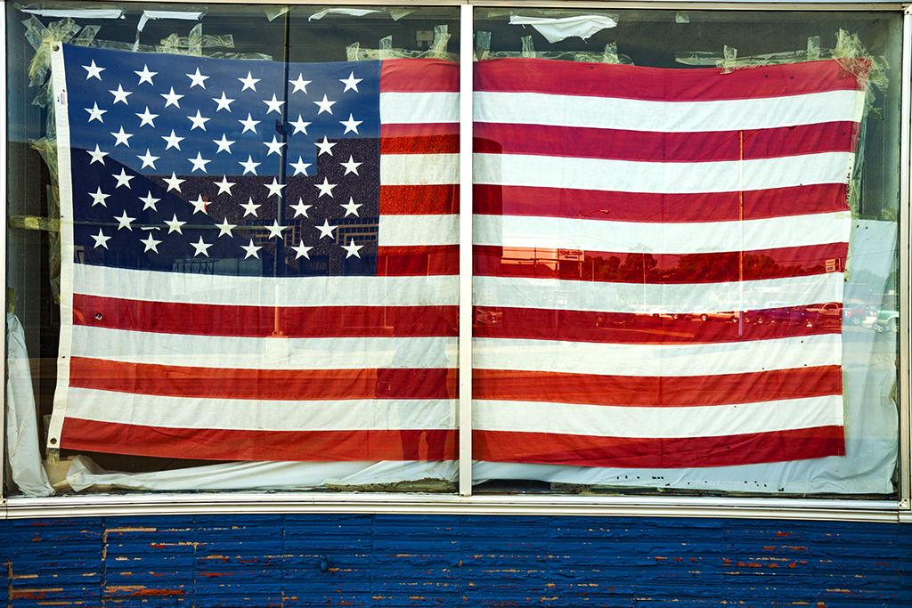 Flag-in-shuttered-store's-window--McCook