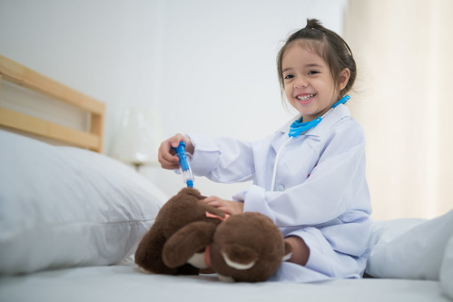 Small girl inject the Teddy Bear by doctor toy set on the bed in bedroom