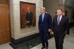 U.S. Secretary of State John Kerry and Canadian Foreign Minister John Baird pass a portrait of former Prime Minister Brian Mulroney as they two prepare to leave Parliament Hill in Ottawa, Canada, on October 28, 2014, after the Secretary visited to pay condolences following last week's attacks and for a series of bilateral meetings. [State Department photo/ Public Domain]