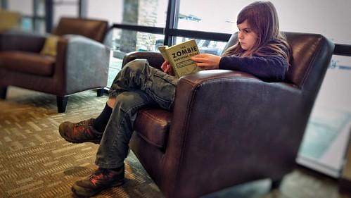Setting a good example for younger kids. Reading The Zombie Survival Guide, by the author of World War Z. Seen in the pediatric dentist office. #thezombiesurvivalguide  #reading #literacy #dentist #pediatricdentist #waitingroom #kid #composure #pokerface