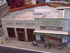 "A model of a 1930s railway station in grey stone, with a branch of the National Provincial Bank on its left.  The station frontage reads ""Southern Railway"" and a projecting canopy reads ""To London in 17 Minutes Cheap Tickets Daily""."