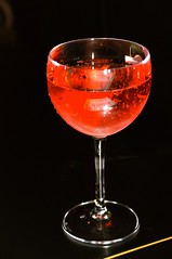 distilled beverage(0.0), wine glass(1.0), red(1.0), glass(1.0), drink(1.0), cosmopolitan(1.0), cocktail(1.0), martini(1.0), alcoholic beverage(1.0),