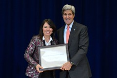 U.S. Secretary of State John Kerry congratulates an employee representing the Bureau of Educational and Cultural Affairs for winning the Telework Achievement Award at the U.S. Department of State's Work-Life Balance Month event in Washington, D.C., on October 23, 2014. [State Department photo/ Public Domain]
